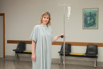 Woman holding a drip stand while walking
