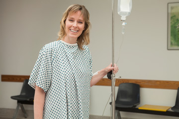 Smiling woman holding a drip stand while walking