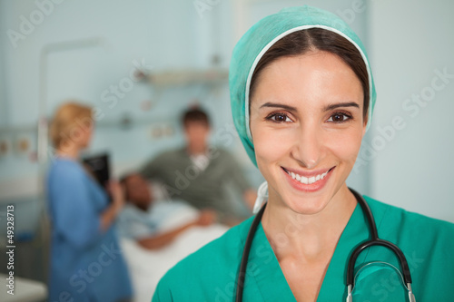 Nurse smiling next to a medical bed