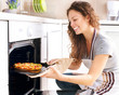 Happy Young Woman Cooking Pizza at Home