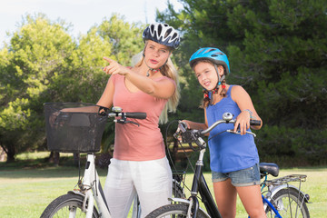 Mother pointing a route out to daughter on bikes