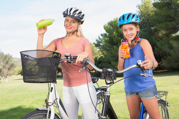 Smiling mother and daughter enjoying a drink while on bikes