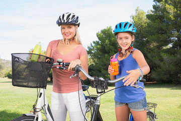 Mother and daughter holding water bottles on bikes