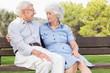 Elderly couple sitting on bench talking