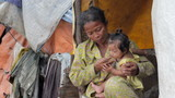 Mother feeding baby in cambodian slums, close to dump area