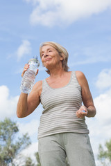 Smiling mature woman in sportswear drinking water