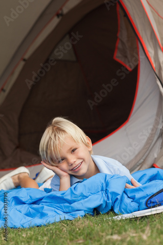 Cute little boy lying on sleeping bag