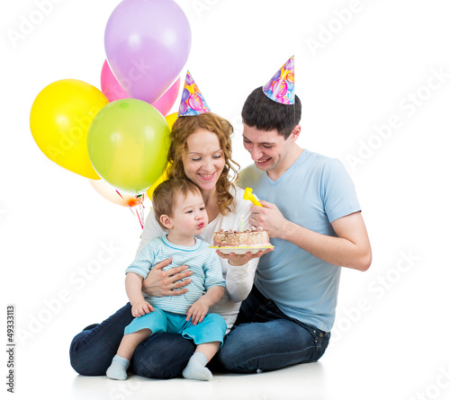 kid boy with parents celebrating birthday  and blowing candles o