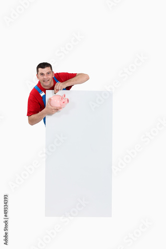 craftsman holding a pig bank and a blank poster