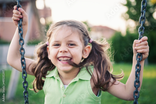 Little smiling girl swinging close up portrait.