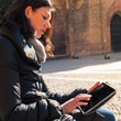 Woman using tablet in Saint Stephen square, Bologna, Italy.