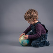 Little kid playing with globe. Studio shot.