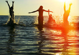 Silhouettes of people jumping in ocean - Fine Art prints