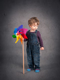Young kid portrait with windmill over grunge background.