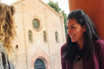 Two girls talking outdoors in S. Stephen square, Bologna, Italy.