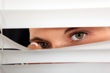 Closeup of a woman's eyes spying through blinds