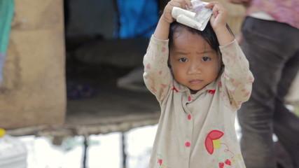 Cambodian kid holding money in slum, shacks at background