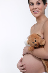 Pregnant woman hugging her belly and a teddy bear