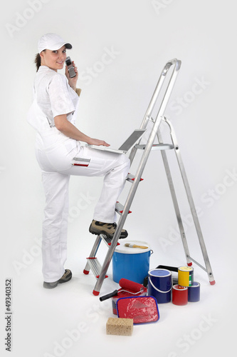 Female decorator with a phone and laptop