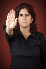 Hispanic woman with her hand extended signaling to stop