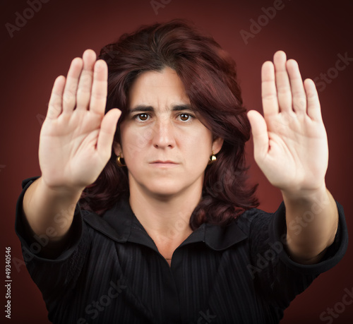 Hispanic woman with her two hands extended signaling to stop