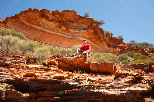 Man sitting bottom of colourful layered rock