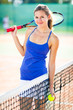 Portrait of a pretty young tennis player on the court
