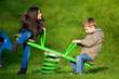enfants jouant a la balançoire dans un parc de jeu