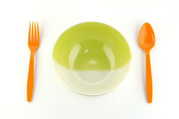green white bowl with orange spoon and fork isolated on white ba