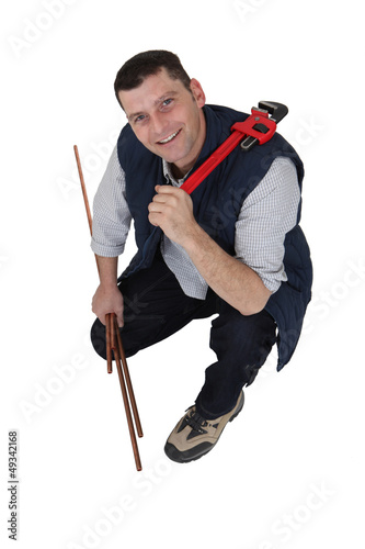 A plumber with copper pipes and a wrench.