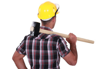 Man carrying sledge-hammer over shoulder