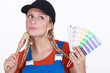 blonde painter looking inspired holding color chart and brush