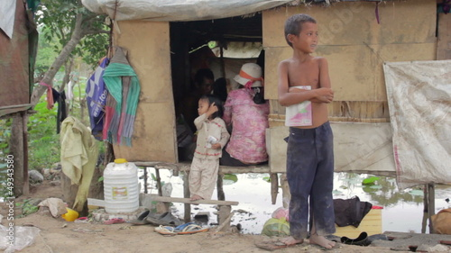 Boy in slum holding book, background his family in shack