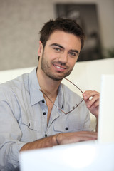 Man with laptop removing glasses