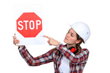 Female laborer pointing stop sign