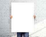 man holding white poster