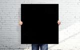 man holding black poster