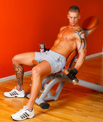 Handsome man with muscles lift a dumbbell