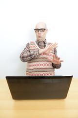 Nerd mit abwehrender Haltung vor dem Laptop