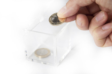 Poor Euro Savings. Hand depositing one euro coin in a  box.