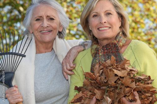 Two women raking leaves