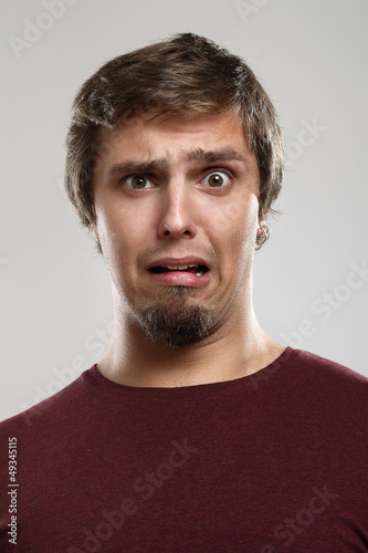 Portrait of young man with scared expression