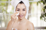 Happy young woman cleansing her face poster