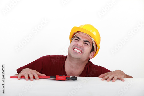 Grunting tradesman trying to lift himself up onto a ledge