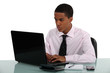 Young businessman hard at work in front of laptop