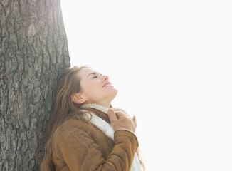 Happy young woman leaning against tree in winter park