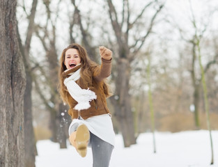 Happy young woman hitting snow with leg