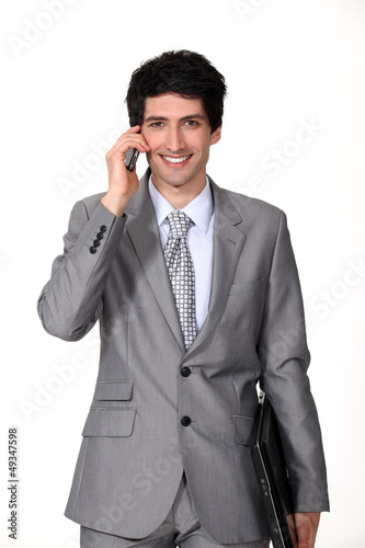 A businessman holding a phone and a laptop.