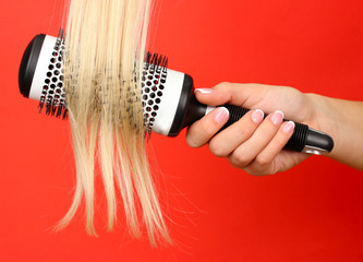 Blond curls brushing comb on color background