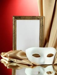 White mask, empty frame and golden silk fabric,